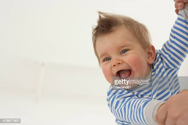 Laughing baby boy hand in hand with his mother