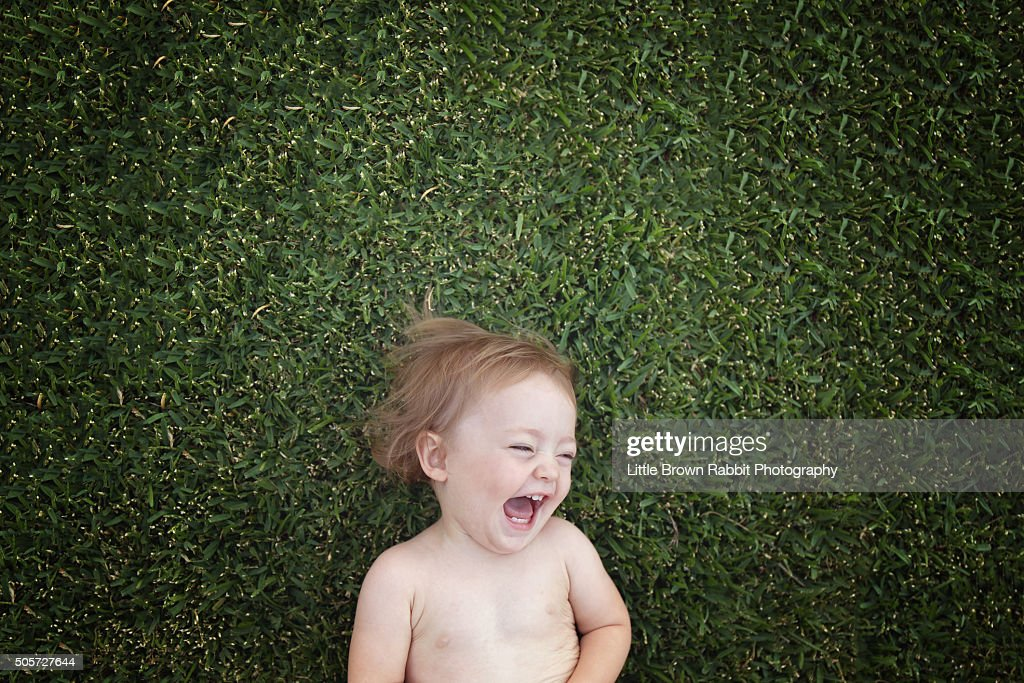 Laughing Baby Lying on Green Grass : Stock Photo