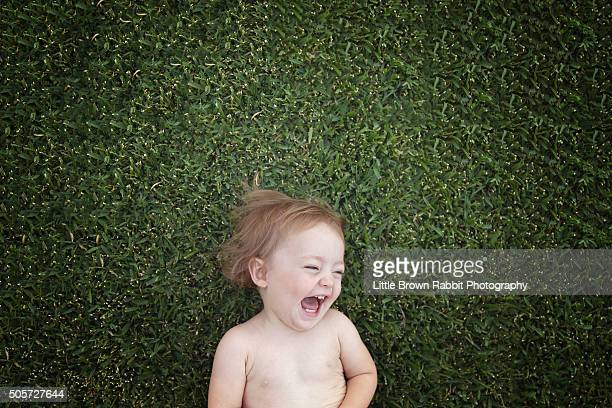 Laughing Baby Lying on Green Grass