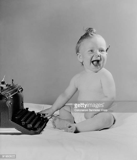 laughing baby using a typewriter - constance bannister stock photos and pictures