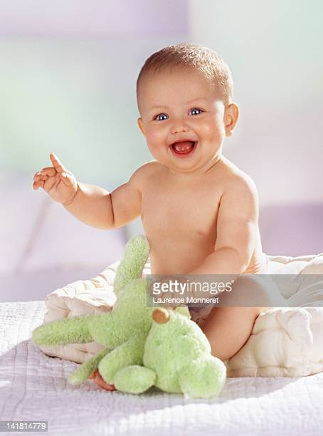 Laughing barechested baby raising finger