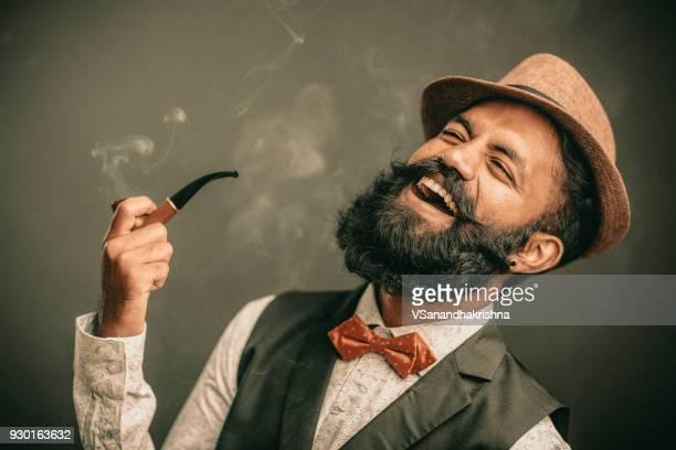 riendo barbudo joven con sombrero y fumador - objeto masculino fotografías e imágenes de stock
