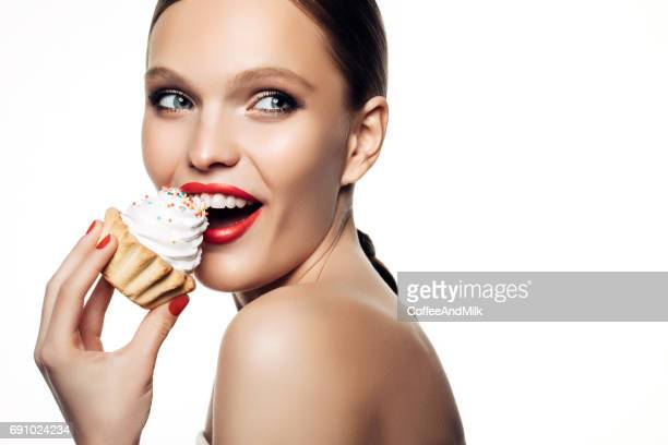 Laughing beautiful women hold little colorful cake