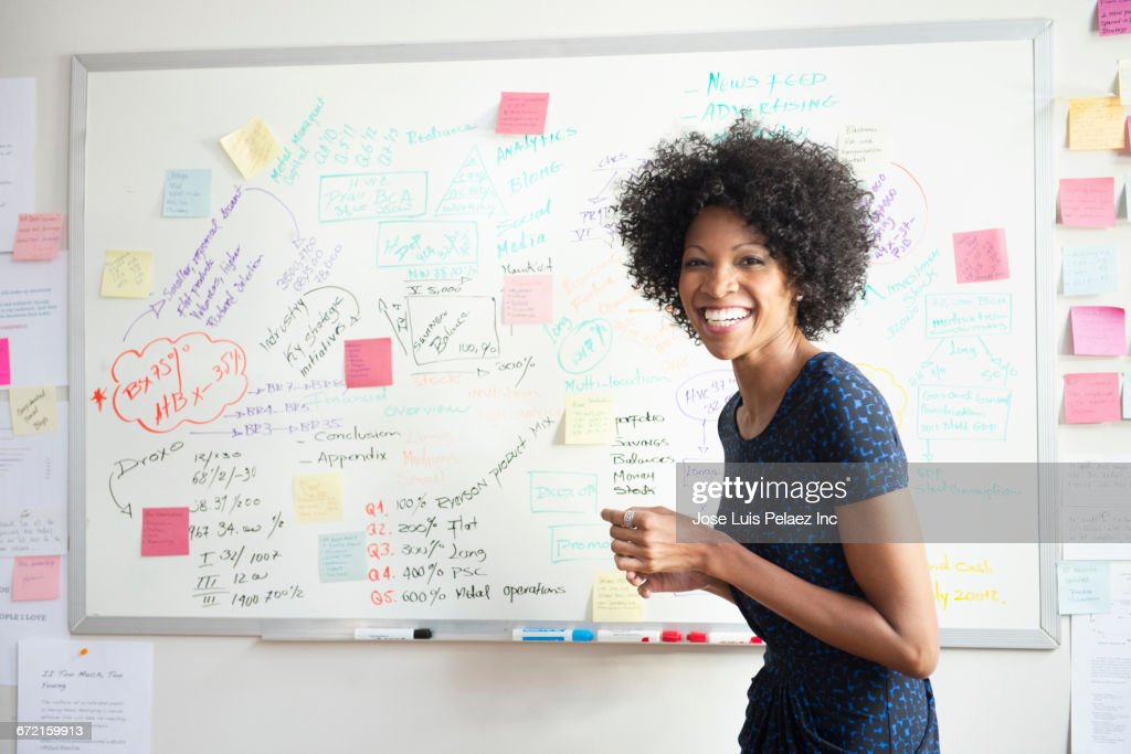 laughing black businesswoman making presentation at whiteboard stock