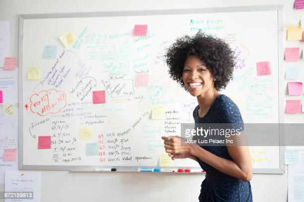 laughing black businesswoman making presentation at whiteboard - zakelijke kleding stock pictures, royalty-free photos & images