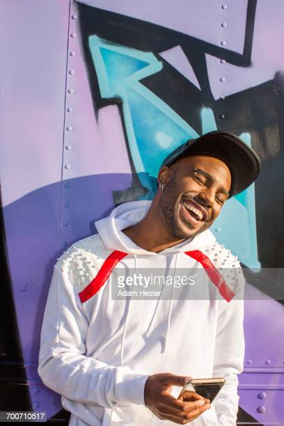 laughing black man texting on cell phone - lilac fashin stock pictures, royalty-free photos & images