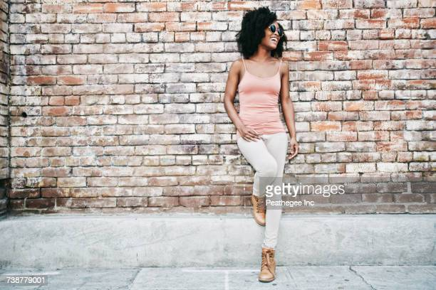 Laughing Black woman leaning on brick wall