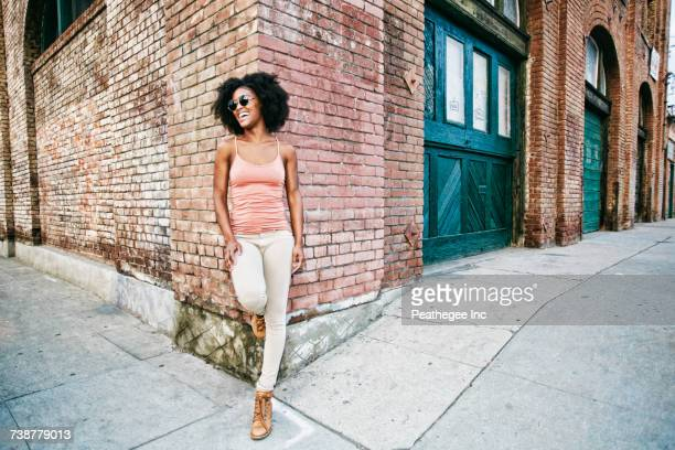 Laughing Black woman leaning on corner of brick building