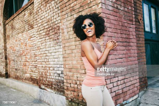 Laughing Black woman standing near corner of brick building