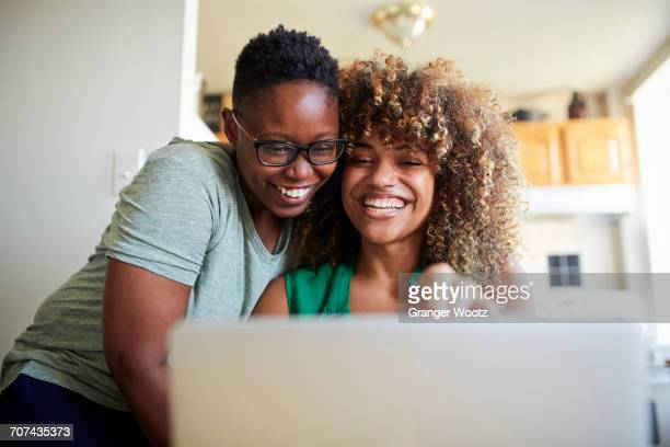 laughing black women hugging and using laptop - gay couple stock pictures, royalty-free photos & images