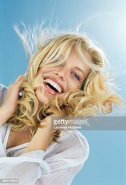 laughing blond girl holding her hair blown by wind - frau bluse durchsichtig stock-fotos und bilder