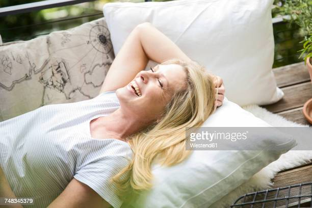 Laughing blond woman relaxing on balcony