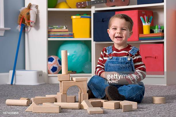 laughing boy building with wooden toy blocks, horizontal - childhood stock pictures, royalty-free photos & images
