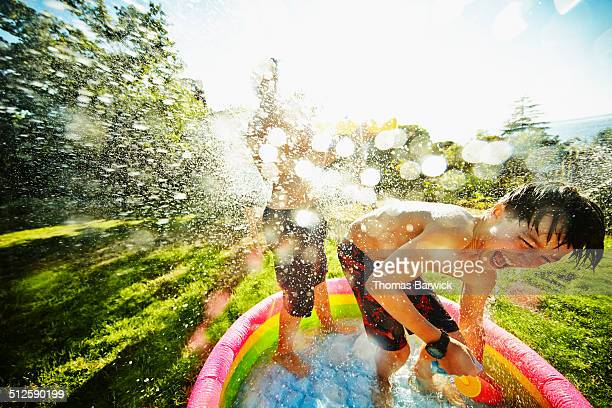 Laughing boy having a water fight with friends
