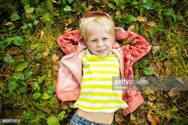 laughing boy laying on the autumn leaves - september stock pictures, royalty-free photos & images