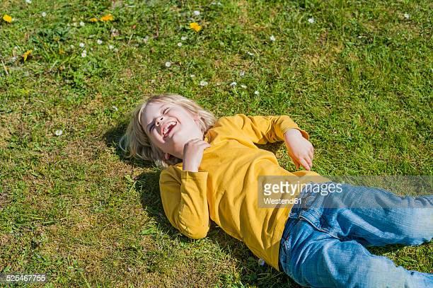 Laughing boy lying in meadow