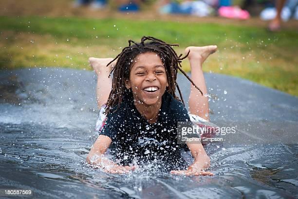 laughing boy on schoolyard slip n slide