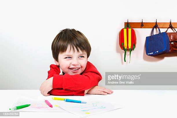 Laughing boy with drawings in the classroom