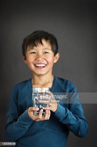 Laughing boy with glass of water in his hand