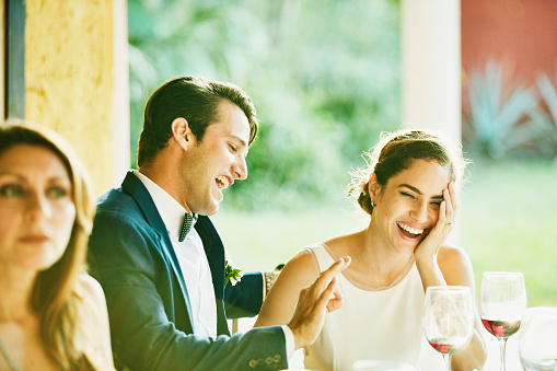 Laughing bride and groom at outdoor reception dinner - gettyimageskorea