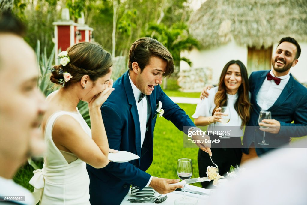 Laughing bride and groom cutting cake for guests during outdoor wedding reception : Stock Photo