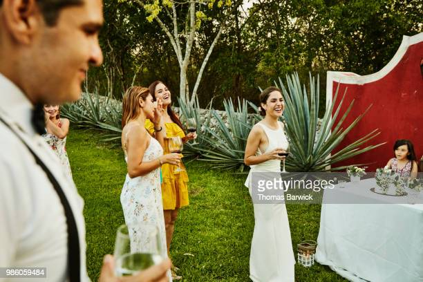 laughing bride at outdoor wedding reception with friends - wedding guest stock pictures, royalty-free photos & images