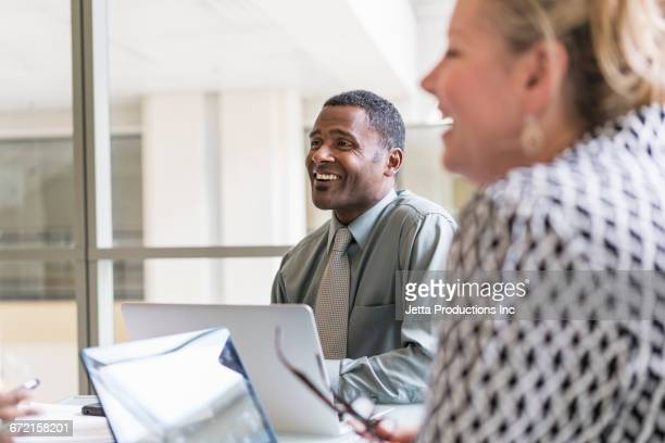 Laughing business people using laptops in meeting