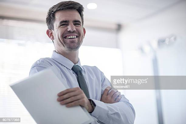 Laughing businessman holding papers