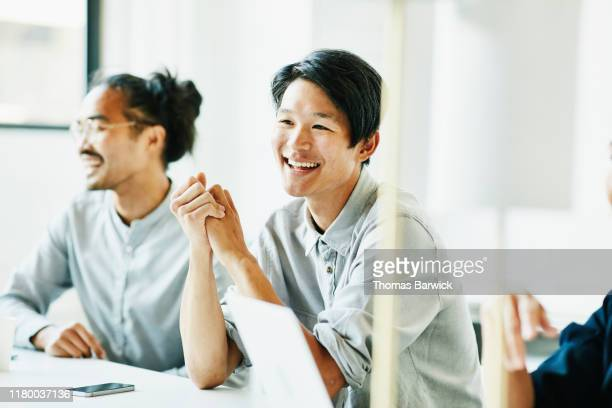 laughing businessman in discussion with colleagues during meeting in office conference room - diversity stock pictures, royalty-free photos & images