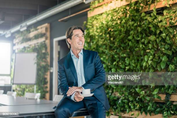 laughing businessman in green office with cup of coffee - green suit stock pictures, royalty-free photos & images
