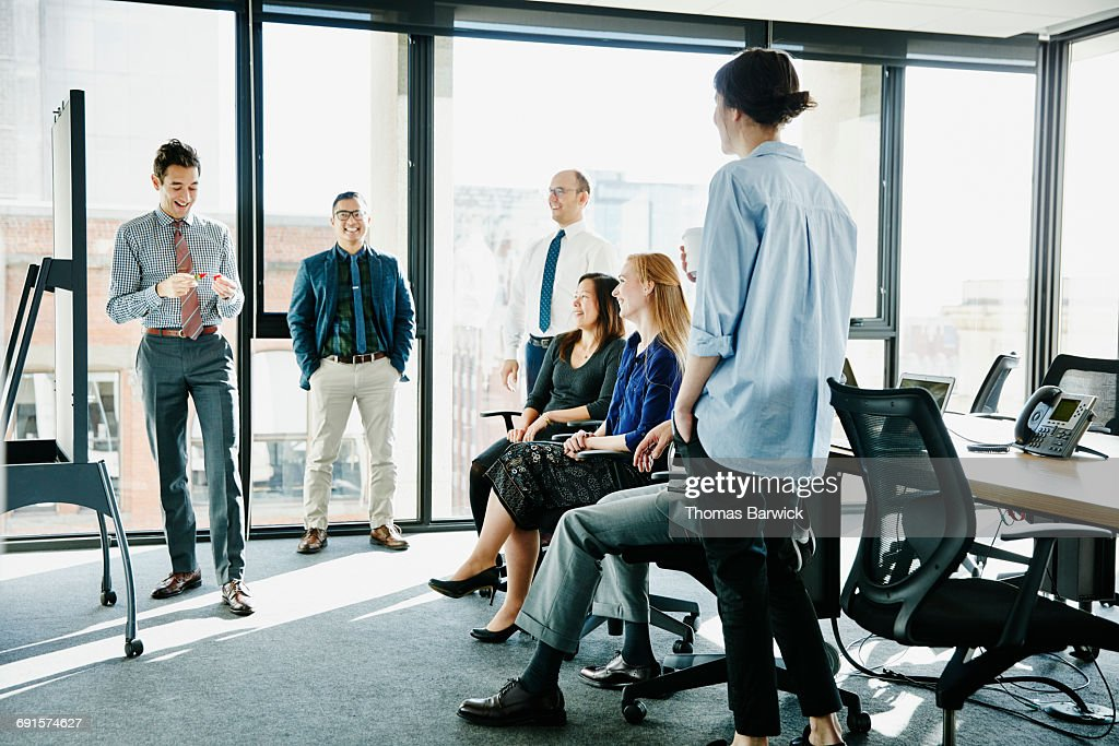 Laughing businessman leading team meeting : Stock Photo
