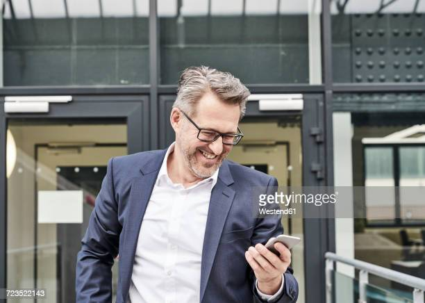 Laughing businessman looking at cell phone