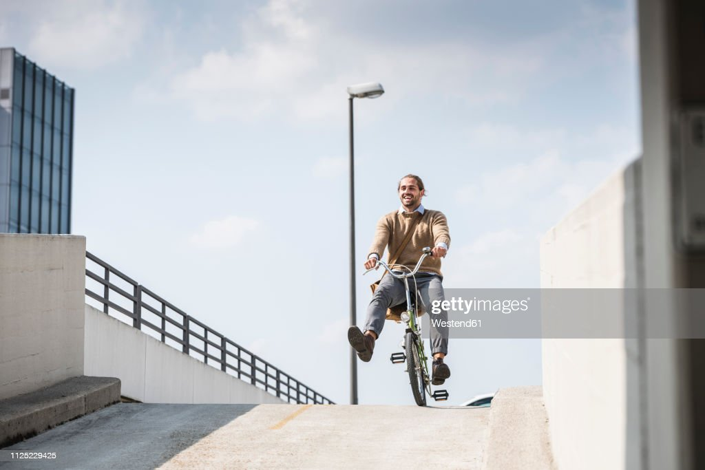 Laughing businessman riding down a ramp on his bicycle : Stock-Foto