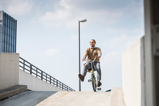 Laughing businessman riding down a ramp on his bicycle - gettyimageskorea