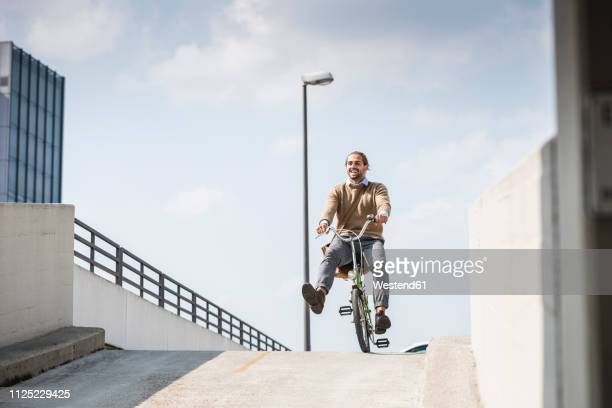 laughing businessman riding down a ramp on his bicycle - radfahren stock-fotos und bilder
