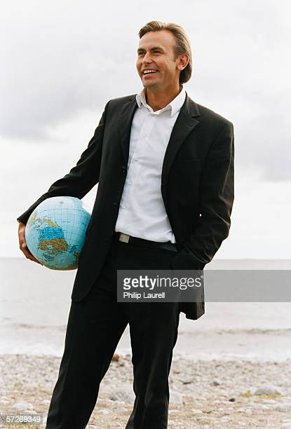 A laughing businessman standing on a beach holding a beach ball shaped as a globe.