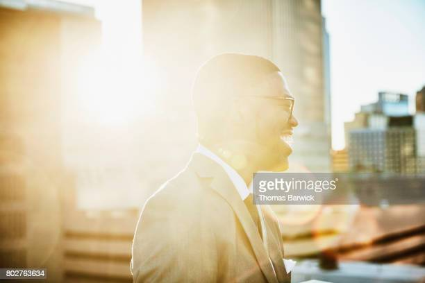 Laughing businessman standing on downtown office deck at sunrise