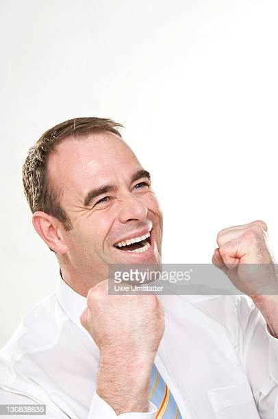 Laughing businessman with clenched fists