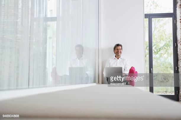 Laughing businessman with pink socks using laptop in office