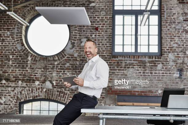 Laughing businessman with tablet in a loft