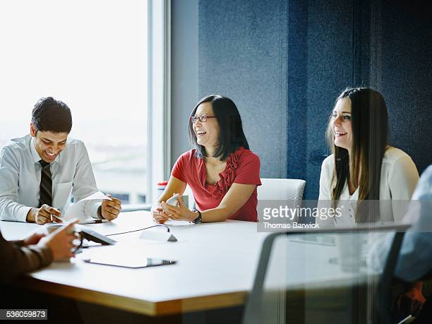 Laughing businesspeople meeting in conference room