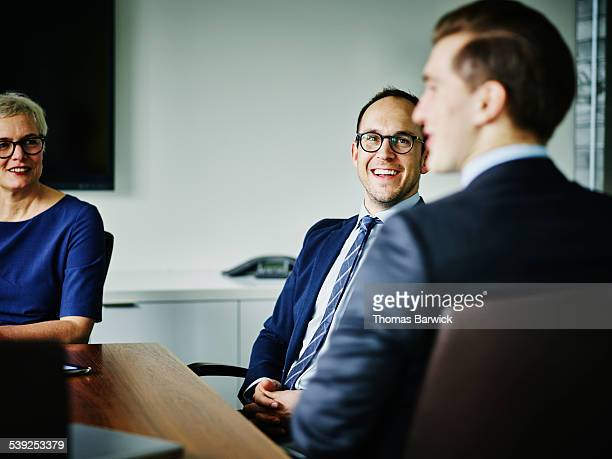 laughing businesspeople meeting in conference room - three people stock pictures, royalty-free photos & images