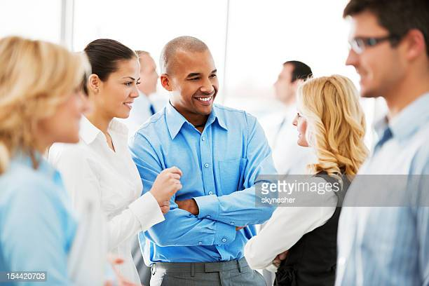 laughing  businesspeople talking in the office. - large group of people stock pictures, royalty-free photos & images