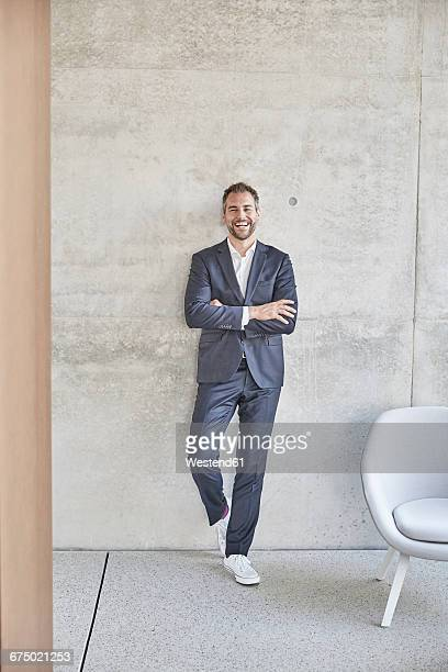laughing businesssman standing at concrete wall - ganzkörperansicht stock-fotos und bilder