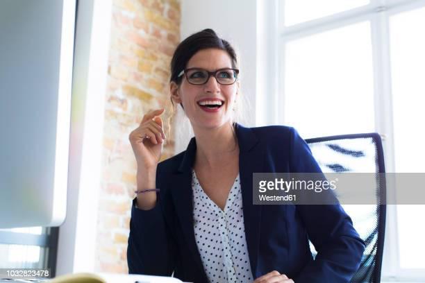 laughing businesswoman at desk in office - solo una donna matura foto e immagini stock
