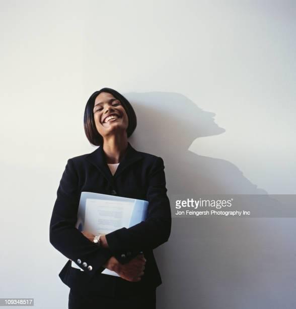 Laughing businesswoman holding binder