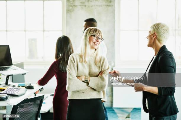 Laughing businesswoman in discussion with coworker in high tech start up office