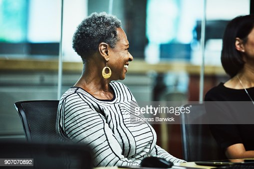 Laughing businesswoman in meeting in office conference room