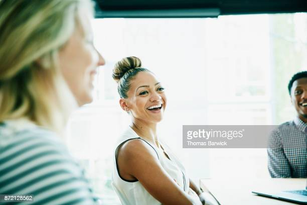 Laughing businesswoman in meeting with clients and coworkers
