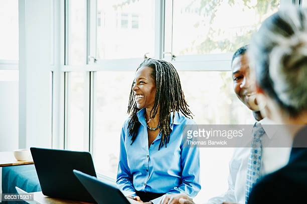 laughing businesswoman in team meeting in office - leanincollection stock pictures, royalty-free photos & images